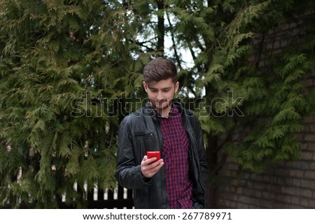 Young businessman reading news in his smartphone - stock photo