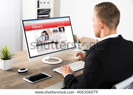 Young Businessman Reading News On Computer At Office - stock photo