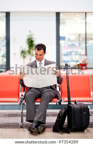 young businessman reading newspaper at airport - stock photo