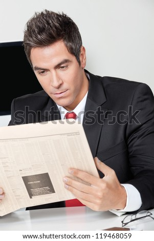 Young businessman reading newspaper at desk in office - stock photo