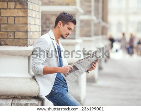 Young businessman reading newspaper outdoors - stock photo