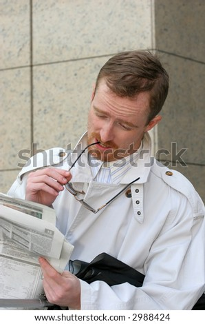 Young businessman reading newspapers and holding Eyeglasses