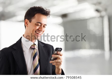 Young businessman receiving a pleasant sms on his cell phone - stock photo