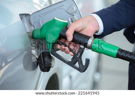Young businessman refueling car tank at fuel station