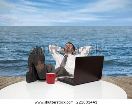 Young businessman relaxes on a pier by the sea