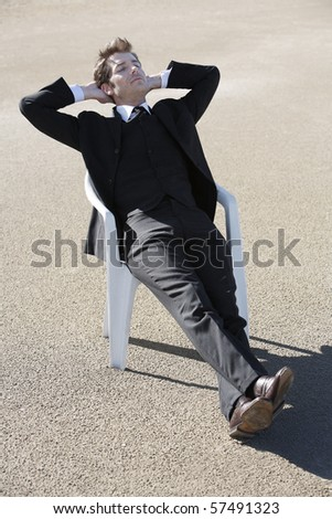 Young businessman relaxing in chair at beach - stock photo