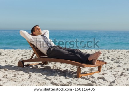 Young businessman relaxing on a deck chair on the beach - stock photo