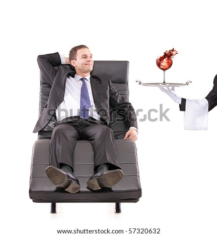 Young businessman relaxing on a sofa while the butler serving a red wine glass isolated on white - stock photo