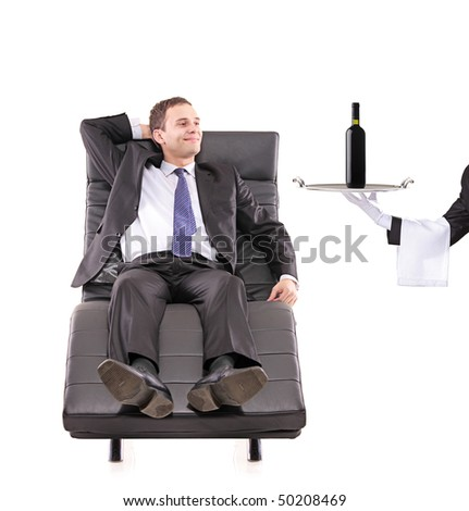 Young businessman relaxing on a sofa while the butler serving a wine bottle isolated on white - stock photo