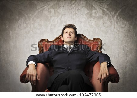 Young businessman relaxing on an armchair - stock photo