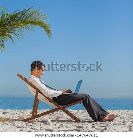Young businessman relaxing on his beach chair using his laptop - stock photo