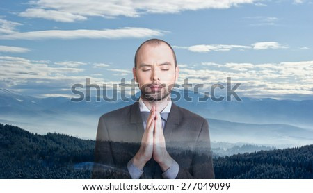 Young businessman relaxing on the mountains background - stock photo
