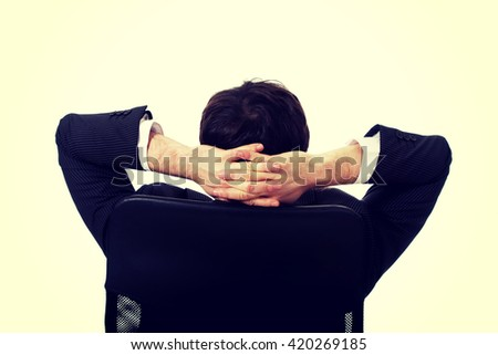 Young businessman resting on armchair. - stock photo
