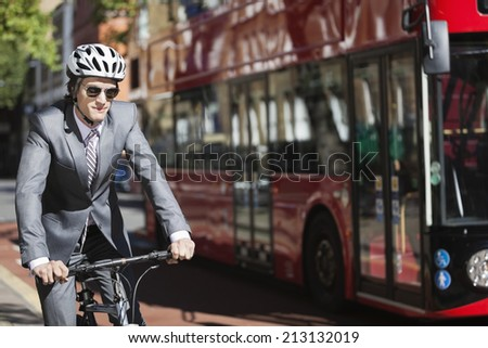 Young businessman riding bicycle by bus on street - stock photo