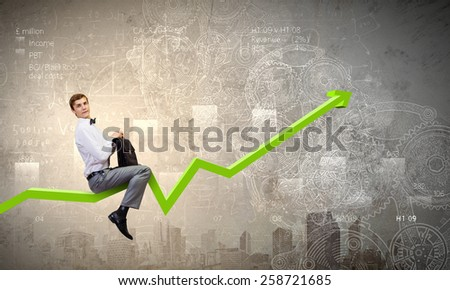 Young businessman riding graph arrow going up - stock photo