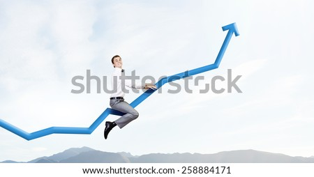 Young businessman riding graph arrow going up