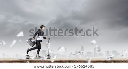 Young businessman riding scooter on roof of building