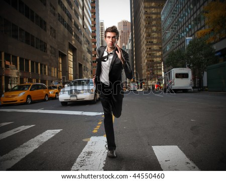 young businessman running in a city street - stock photo