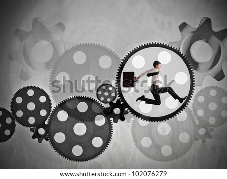 Young businessman running in a gear of a mechanism - stock photo