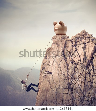 Young businessman scaling a rock to reach a large piggy - stock photo