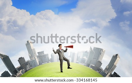 Young businessman screaming emotionally in paper trumpet on cityscape background