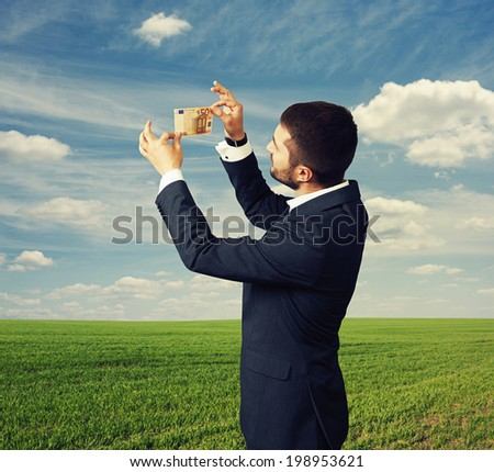 young businessman scrutinizing banknote outdoors - stock photo
