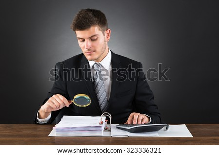 Young Businessman Scrutinizing Invoice With Magnifying Glass - stock photo