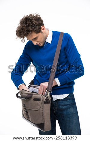 Young businessman searching documents in his bag - stock photo