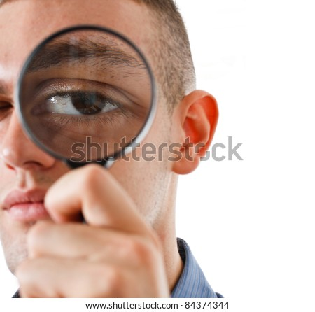 Young businessman searching for something using a magnifying glass