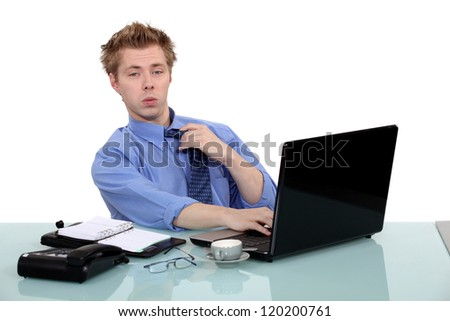 young businessman seated at desk with laptop - stock photo
