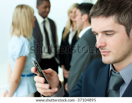 Young businessman sending a text in office with his team in the background - stock photo