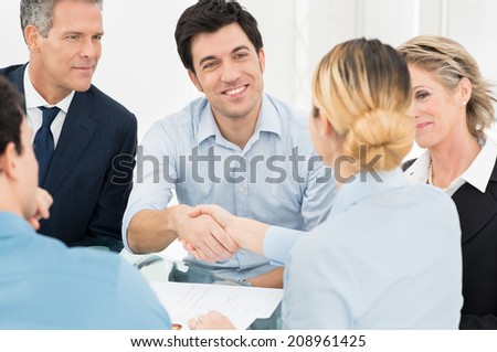 Young Businessman Shaking Hand With Businesswoman In Front Of Colleague - stock photo