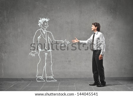 young businessman shaking hands with a man drawn on the wall - stock photo