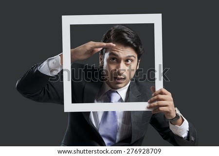 Young businessman shielding eyes while holding frame over black background