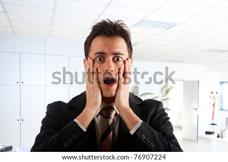 Young businessman shocked in an office environment - stock photo