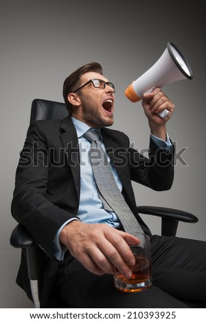 Young businessman shouting and sitting on chair. closeup of guy sitting with megaphone and glass on white background - stock photo