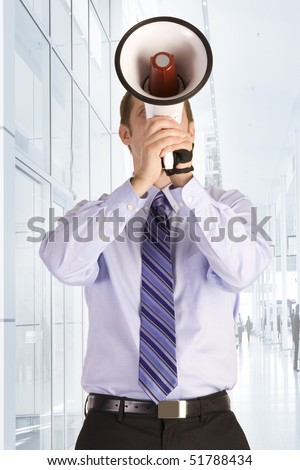 Young businessman shouting into a megaphone. - stock photo