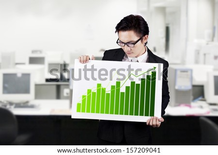 Young businessman showing a business graph board - stock photo