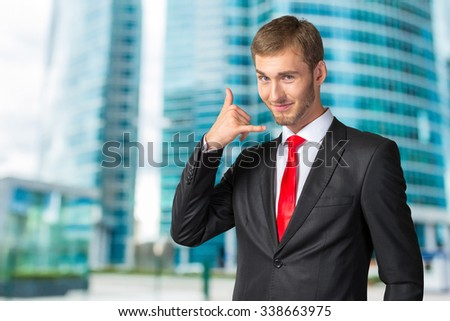 "Young Businessman showing ""Call me"" sign"