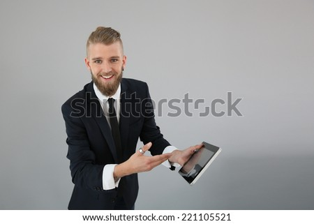 Young businessman showing digital tablet screen - stock photo