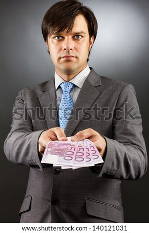 Young businessman showing euro banknotes over gray background - stock photo
