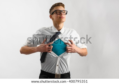 Young businessman showing suit of super hero with copy space under his shirt and tie on gray background