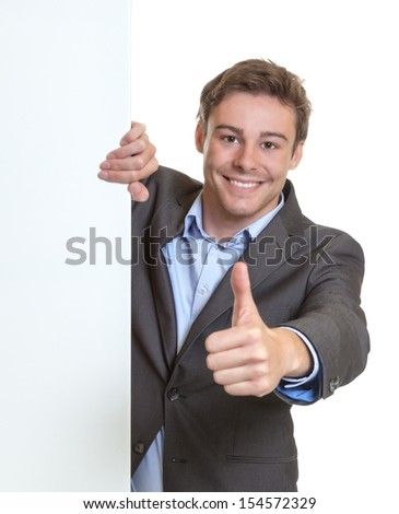 Young businessman showing thumb behind a signboard - stock photo