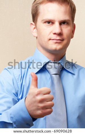 young businessman showing thumbs up sign - stock photo