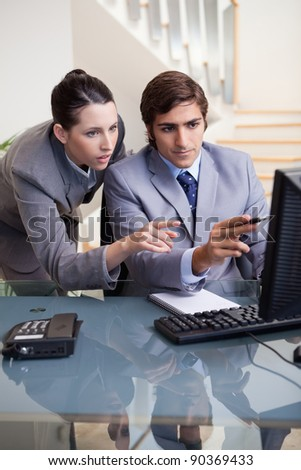 Young businessman showing whats on his screen to his colleagues