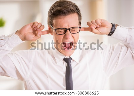 Young businessman shuts his ears with his hands and screaming. - stock photo