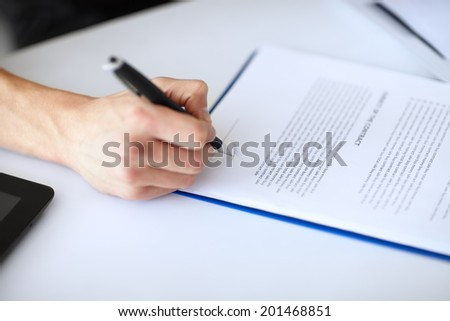 Young businessman signing document at table in white office close-up - stock photo