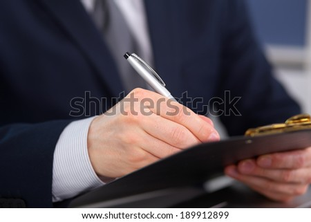 Young businessman signs contract on a black folder