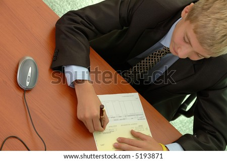 young businessman signs document on workplace.