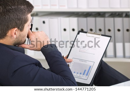 young businessman siting in chair and analyzes work - stock photo